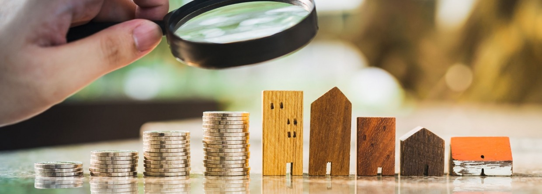 hand met een vergrootglas boven een rij huizen en geld