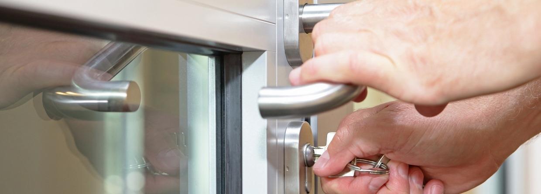 Twee handen doen met een sleutel de deur op slot