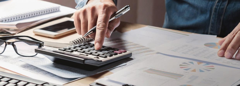 zakenman aan het werk in zijn kantoor met zijn rekenmachine