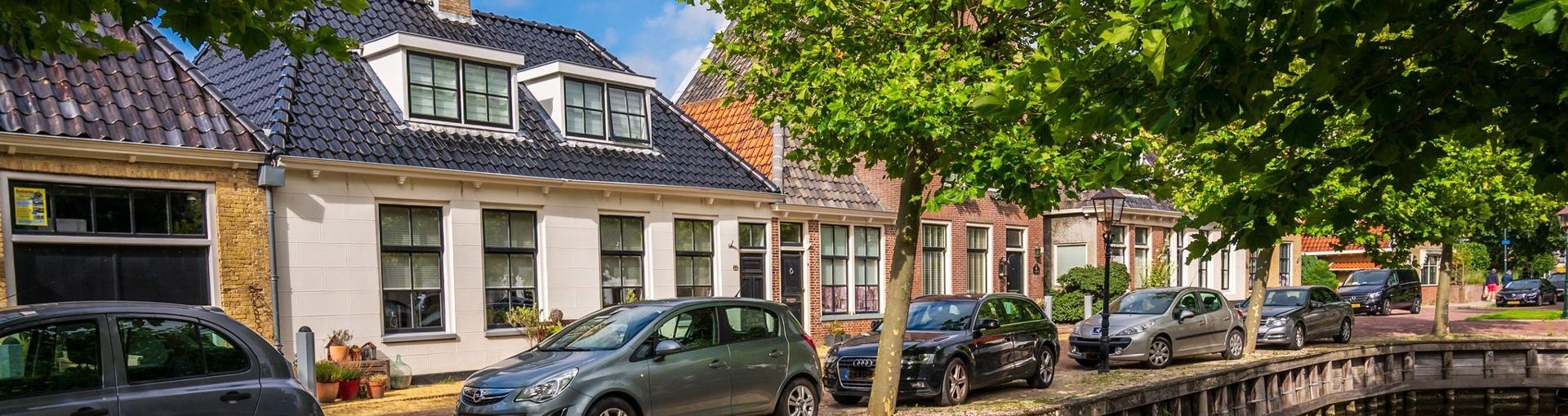 Een straat in Harlingen met huizen en auto's en een bootje in de gracht
