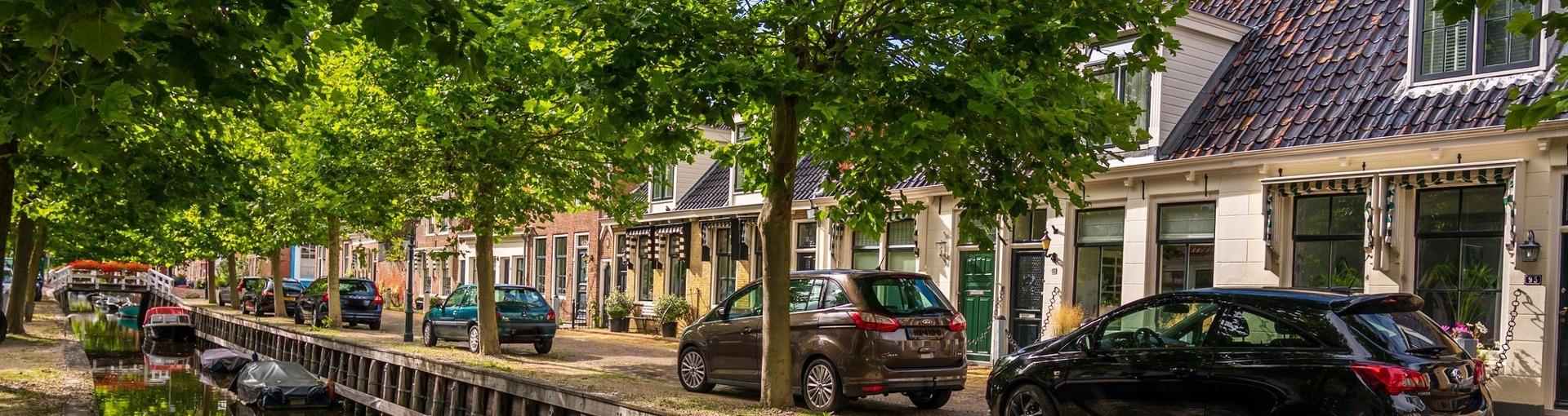 Een straat in Harlingen met huizen en een bootje in de gracht